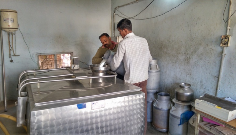 Two men pouring milk into machine