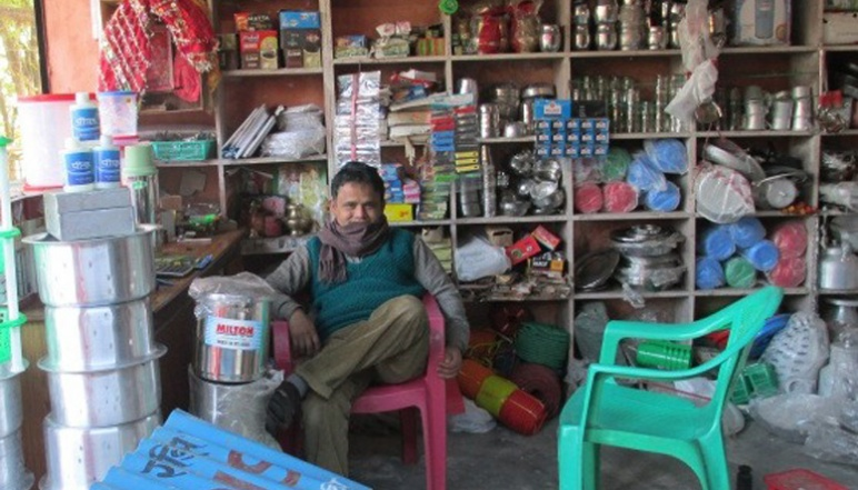 Man sitting in chair in shop that sells water sanitation products