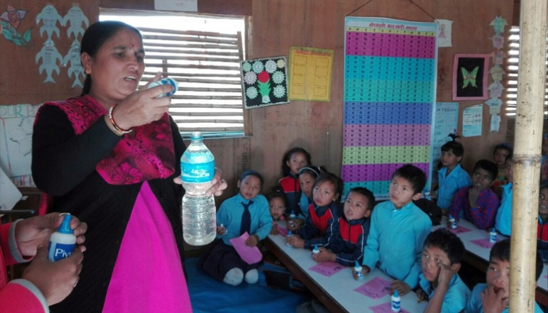 Woman holding water bottle teaching school children how to santize water