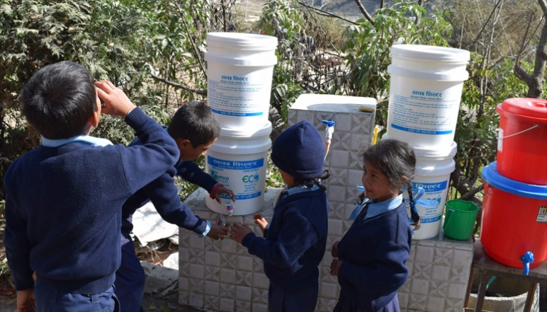 Children getting water from filtered white buckets