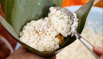 Rice being scooped in leaf bowl